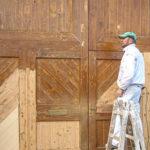 Maler renoviert ein Holztor