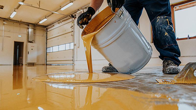 Arbeiter, der einen gelben Epoxidharz-Eimer auf den Boden aufträgt.