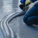 Der Arbeiter trägt graues Epoxidharz auf den neuen Boden auf