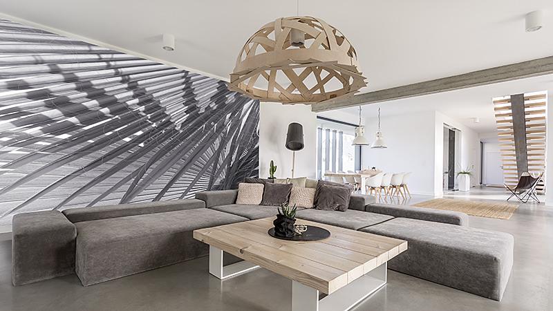 Zimmer mit extra großem Sofa, Holztisch und Fototapete