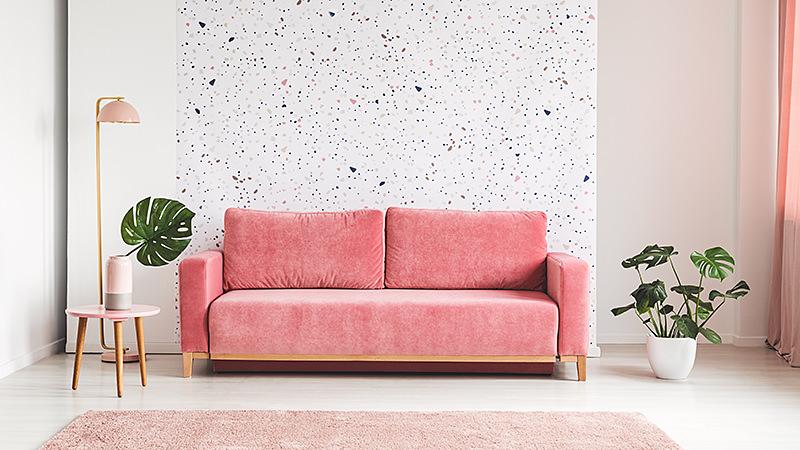 Rosa Couch zwischen Pflanze und Lampe im hellen Wohnzimmer Interieur